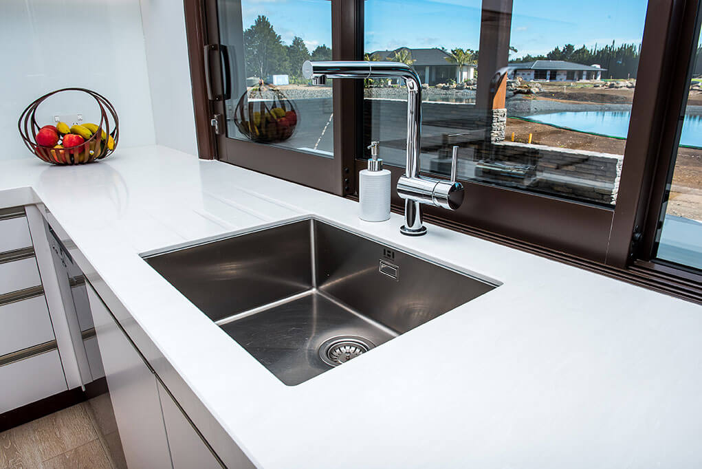 Corian benchtop in Cirrus White with routed drainer grooves.